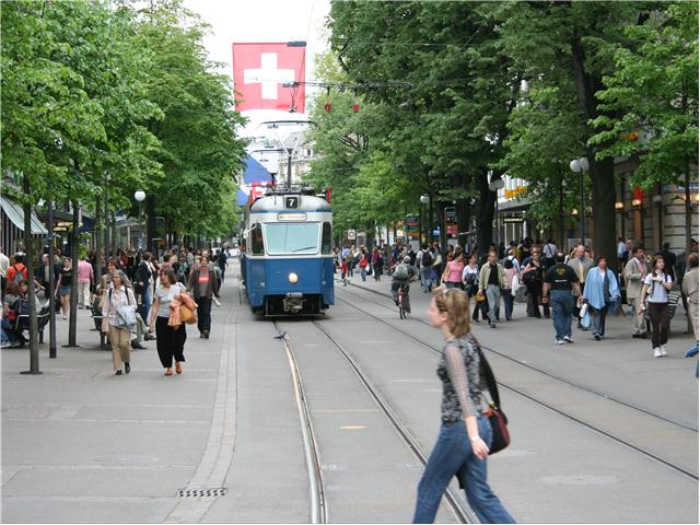 people walking and light rail train in middle
